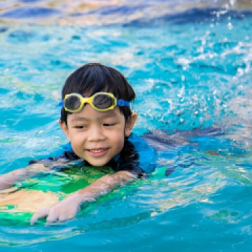 young boy swimming with flutter board