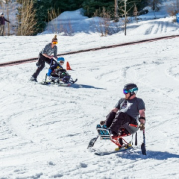 Skiers using sit-skis on the hill