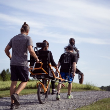 a person being transported by two other people on an adapted bike