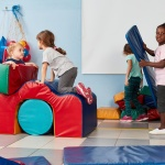 A group of young children playing with gym building blocks