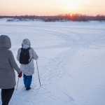 Two older women walking through snow using poles for balance