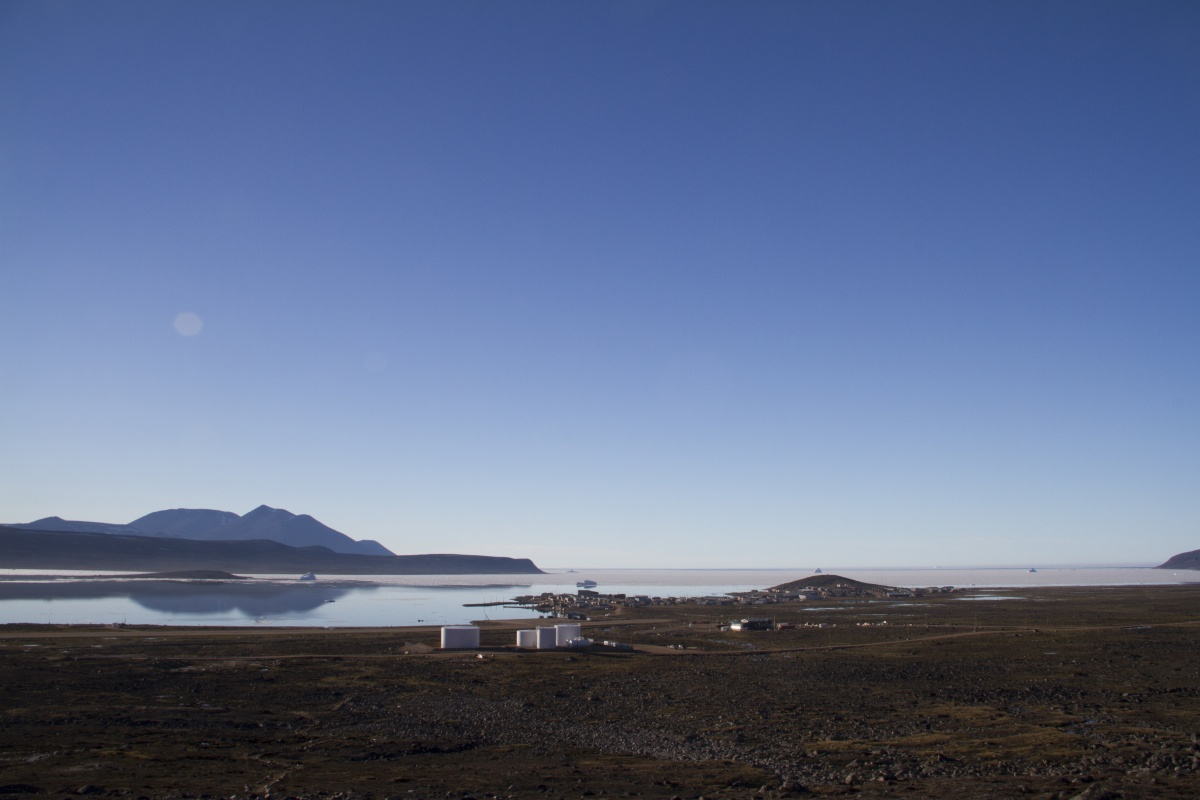 flat land with a few buildings and a mountain in the distance past a small lake - Nunavut