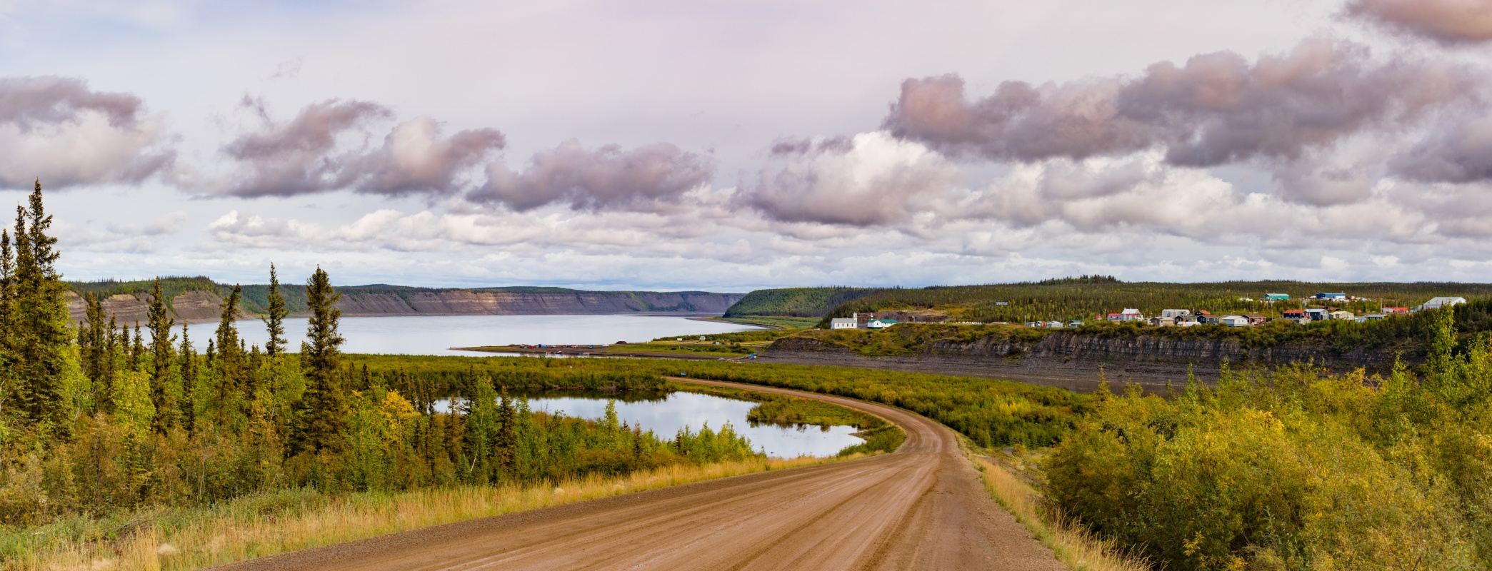 North West Territories arctic landscape of a dirt road, trees and a small lake.