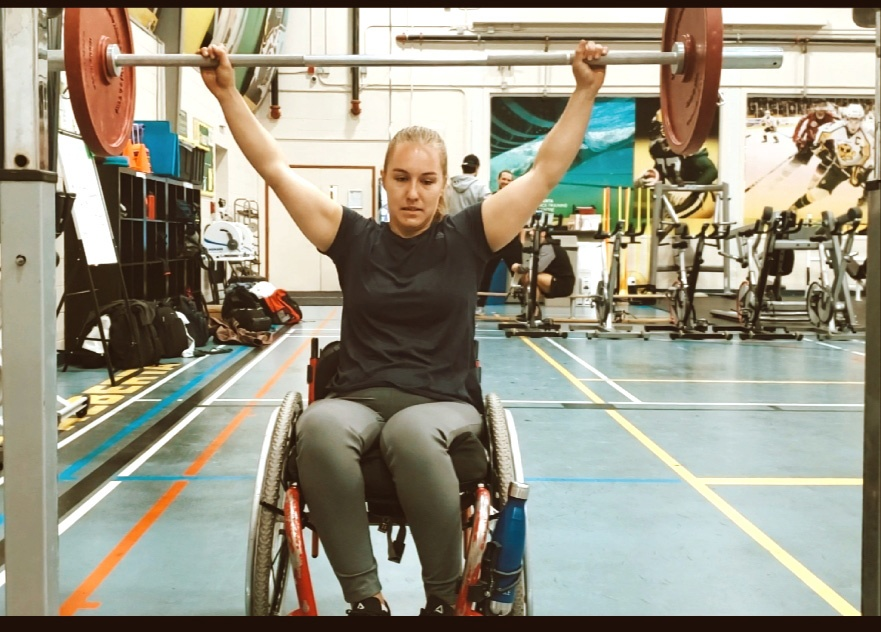 Sierra lifting weights while seated in her wheelchair