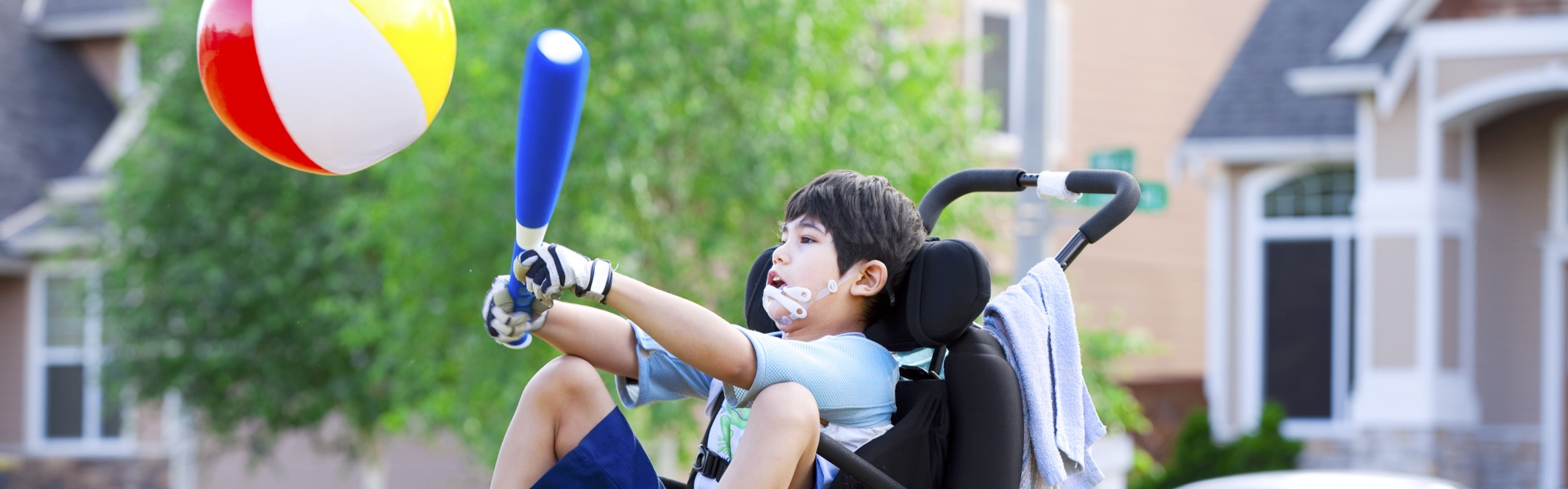 Boy in wheelchair with plastic bat and beach ball