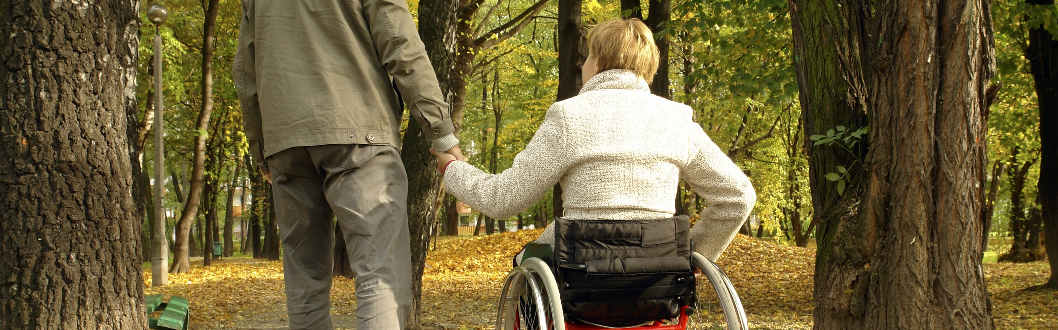 Back view of man holding hands with lady in a wheelchair
