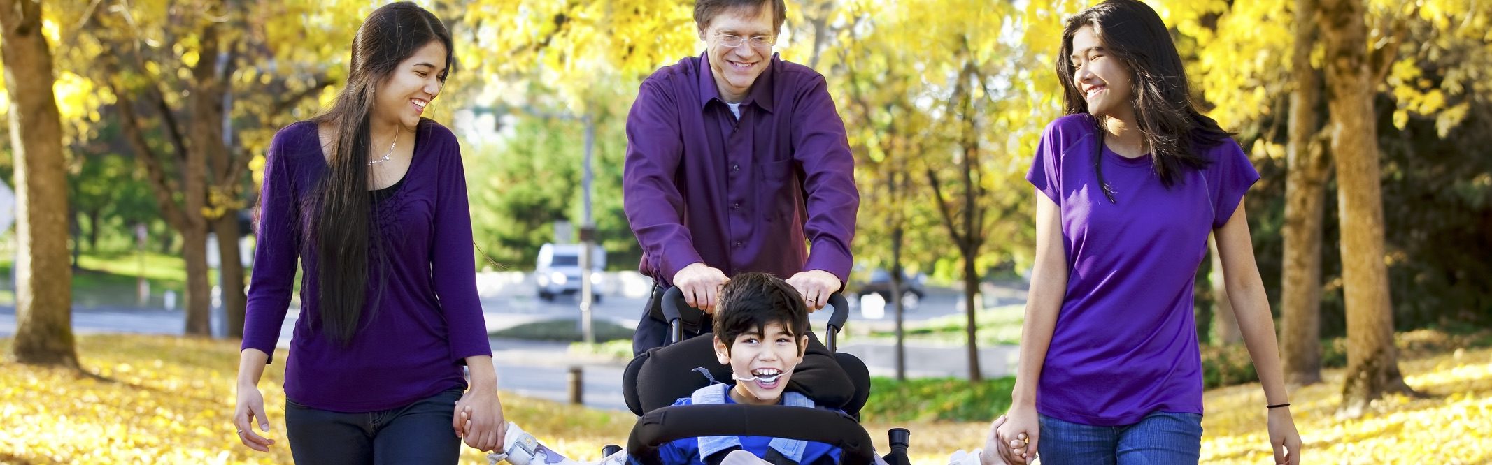 Three people in purple shirts walking with a boy in a wheelchair