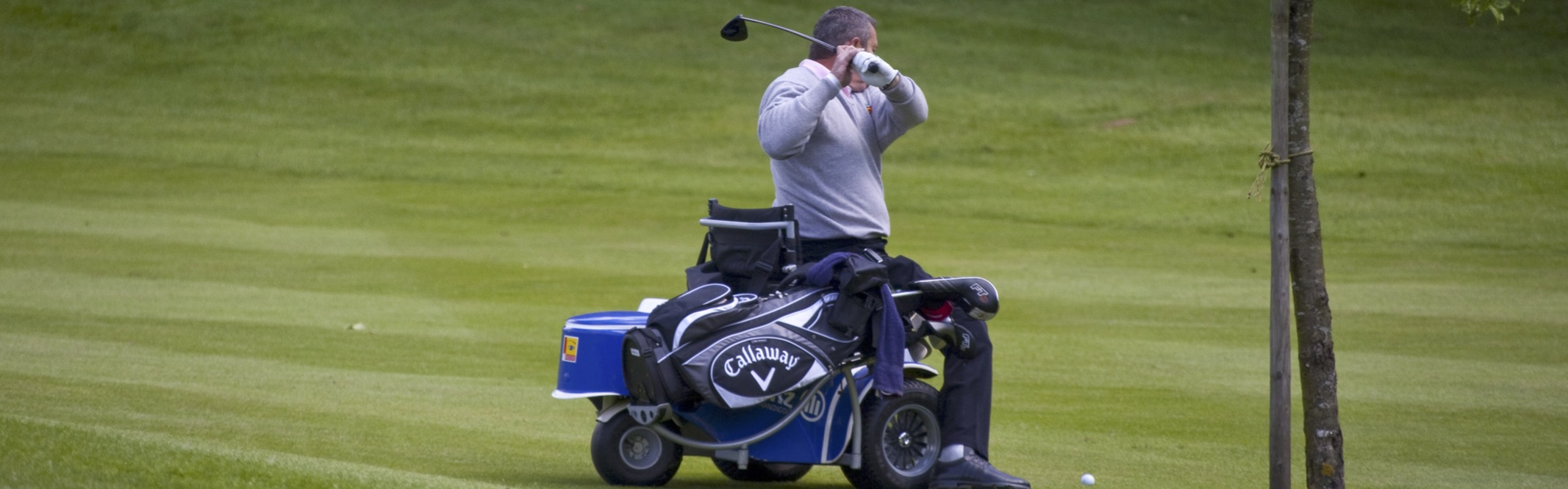 Man in power chair playing golf